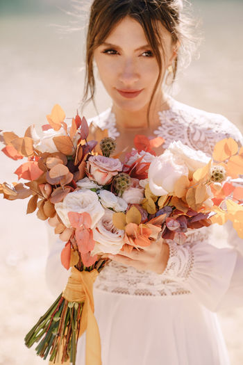 Smiling bride holding flower bouquet outdoors