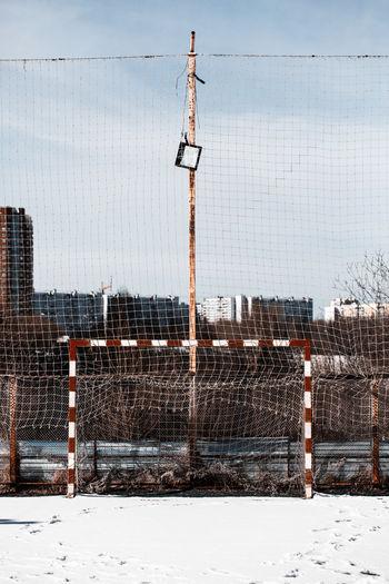 Soccer goal on field against sky during winter