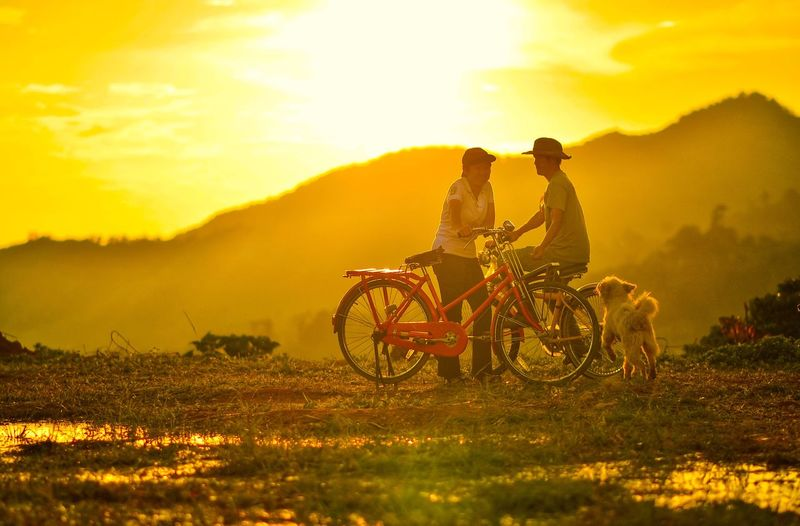 Man and woman with bicycles and pet on field against sky during sunset