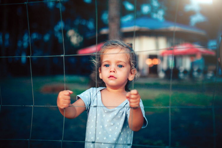 little caucasian girl standing behind the metal grid fence Childhood Child One Person Real People Looking At Camera Cute Portrait Front View Innocence Girls Focus On Foreground Waist Up Holding Lifestyles Casual Clothing Standing Daughter Children Kid Little Girl Hostage Sad Sadness Sad Face Depression Depressed Depression - Sadness Freedom Jail Lonly Lonliness Summer Caucasian Hand Fence Metal Grid