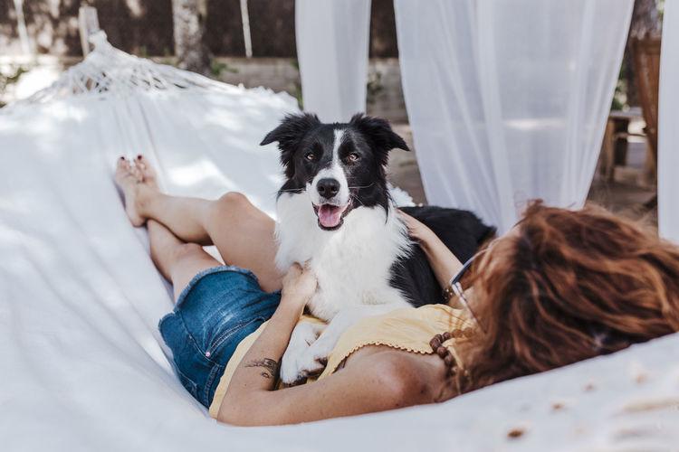 Woman with dog sitting on hammock