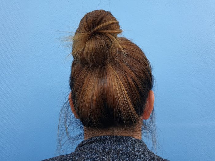 Rear view of woman against blue wall