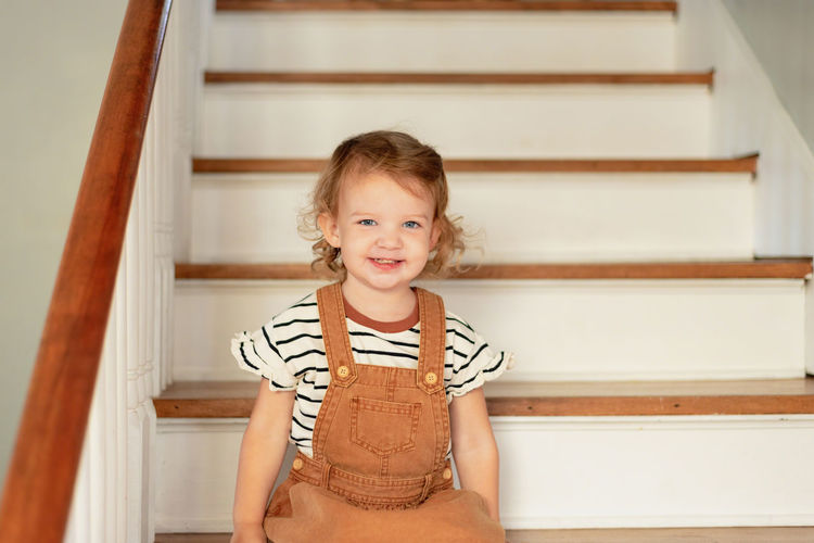 Portrait of cute girl sitting on staircase at home