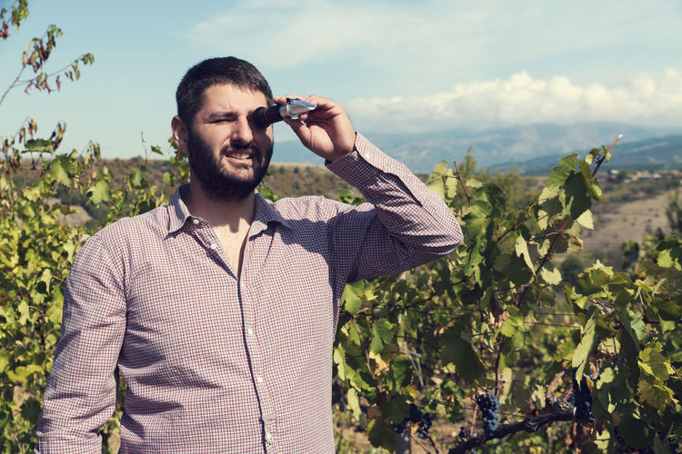 Man looking through refractometer while standing against plants and sky
