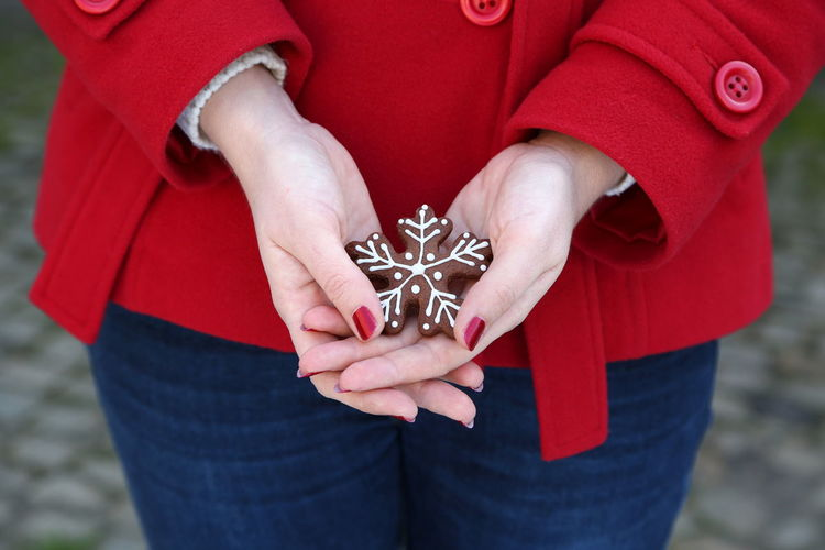 Midsection of woman holding gingerbread cookie during christmas