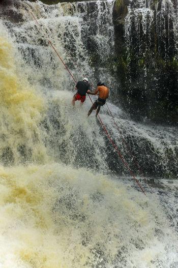 People climbing up waterfell