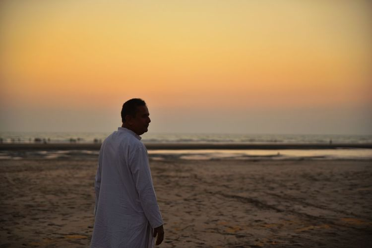 Man standing on beach against sky during sunset