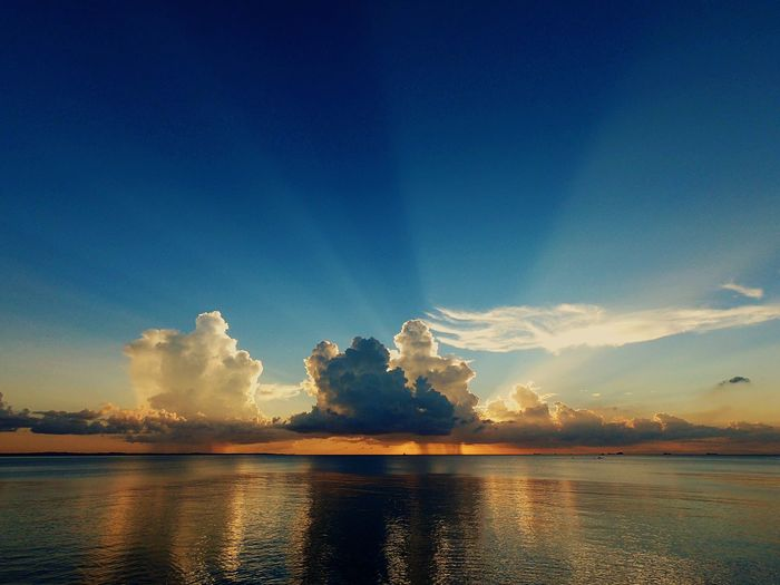 Rain in the sunset Sunrays Sky Water Reflection Scenics - Nature Sunset Beauty In Nature Cloud - Sky Tranquility Tranquil Scene Blue Sea Nature No People Waterfront Idyllic Outdoors Orange Color Horizon Over Water