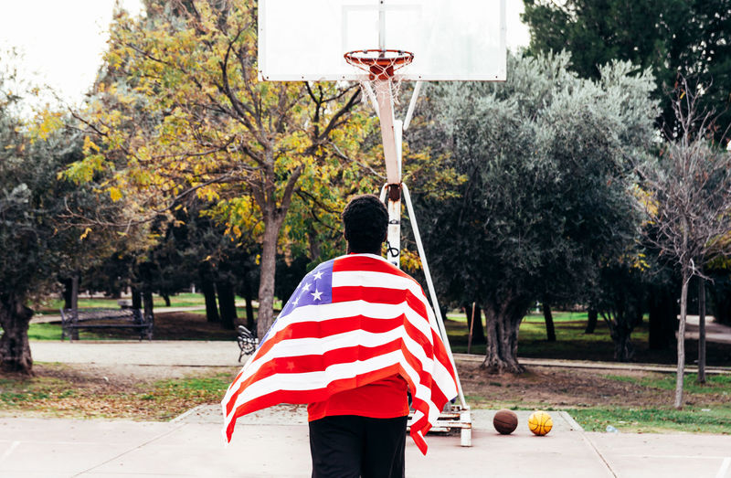 Rear view of young man holding american flag standing on basketball court