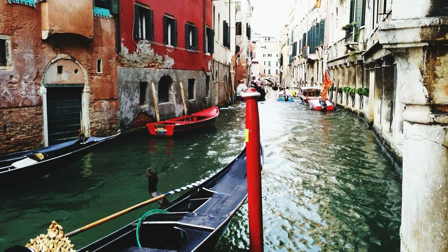 Gondolas In Canal Amidst Buildings In Old Town