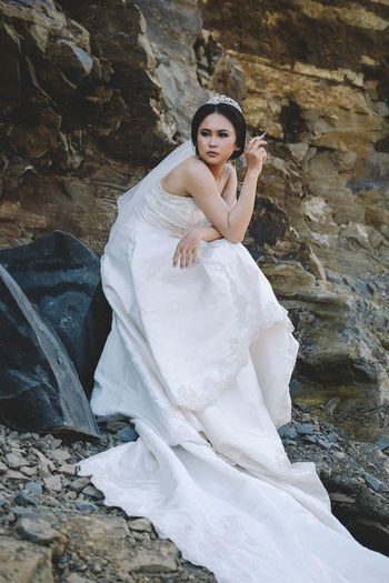 Young beautiful bride sitting against rock formation