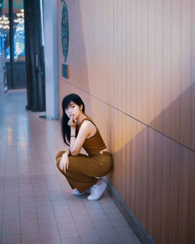 Portrait of woman crouching against wooden wall