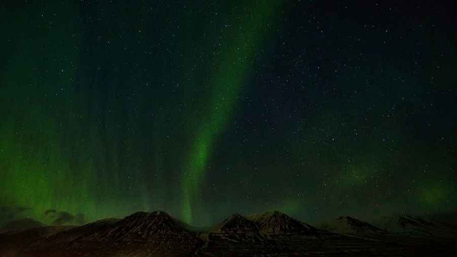 Low angle view of mountain against sky with aurora at night