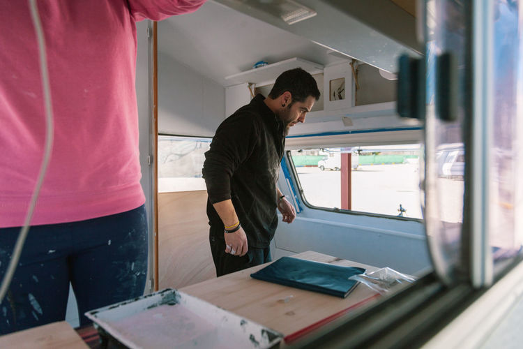 Young couple painting and restoring caravan Standing Two People Men Real People Indoors  Casual Clothing Adult Working Young Men People Occupation Three Quarter Length Waist Up Young Adult Males  Mid Adult Looking Mid Adult Men Table Caravan Restoring Couple Update