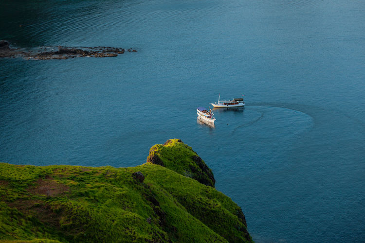 Boats are floating in the blue water of padar island