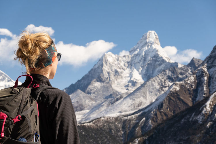 Rear view of woman looking at snowcapped mountains against sky