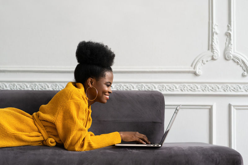 Smiling businesswoman using laptop while lying on sofa at home
