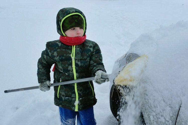 Cute Boy Cleaning Snowcapped Car During Winter