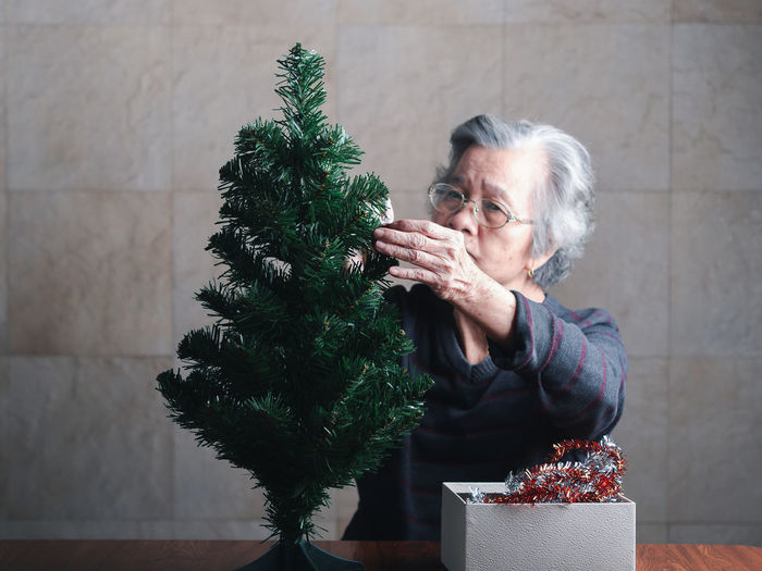 Portrait of a senior woman decorating the christmas tree while sitting in a living room at home.
