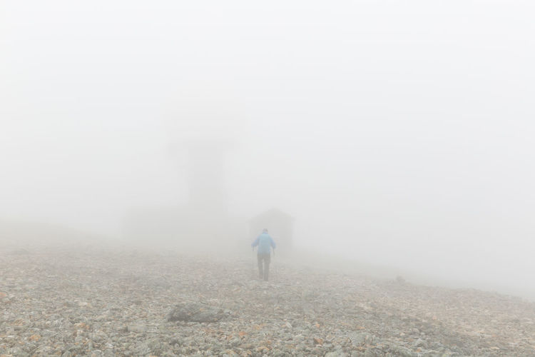 Rare view of hiker walking on fog covered field