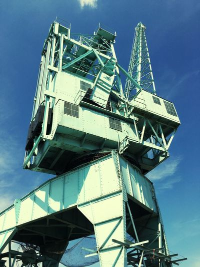 Low angle view of container crane against sky