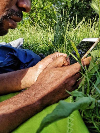 Human Body Part Real People Face Part Black Man Man's Hands Internet Searching Man Using His Phone Man In The Park Mobile Phone Technology Outdoors Communication Man With A Phone Human Hand Cellphone Tree Grass Nature Green Color Green One Man Only Black Man
