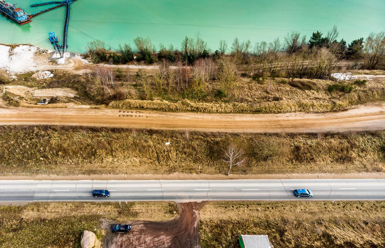 Aerial view of a road and a paved path at the edge of a sand quarry, made with drone Drone  Drone Landscape Edge Path Road Aerial Aerial View Day Field Grass Landscape Nature No People Outdoors Pave Pavement Photo From Above Quarry Road Sand Sky Tree