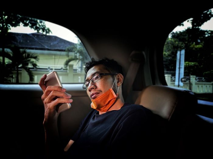 Man using phone while sitting in car