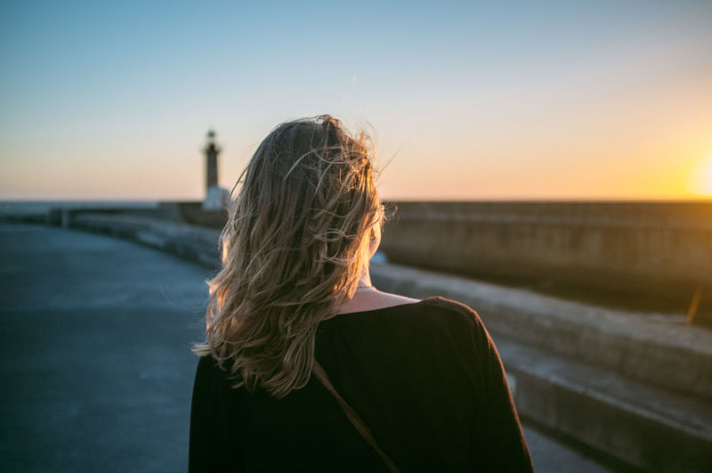 Rear view of woman on promenade against sky during sunset