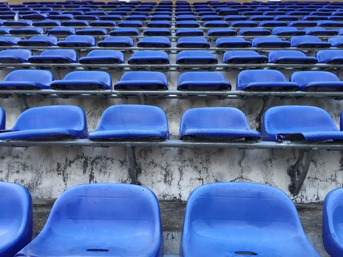 Blue empty chairs in stadium
