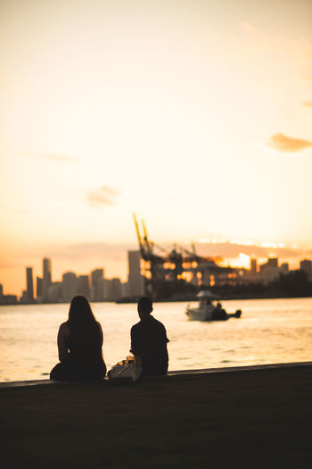 Silhouette people sitting by sea against sky during sunset