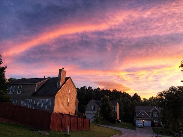 Houses and buildings against sky during sunset