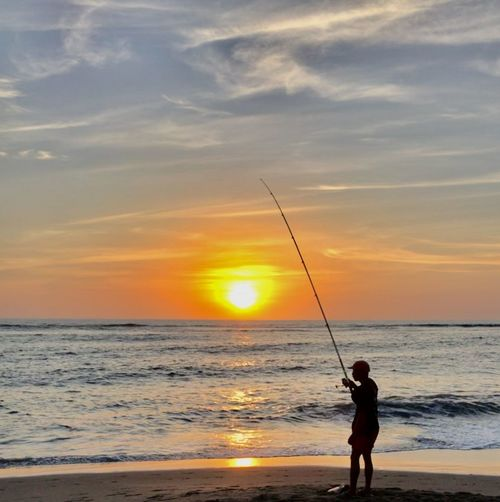 Man fishing at beach against sky during sunset