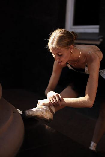 Female ballet dancer stretching at home