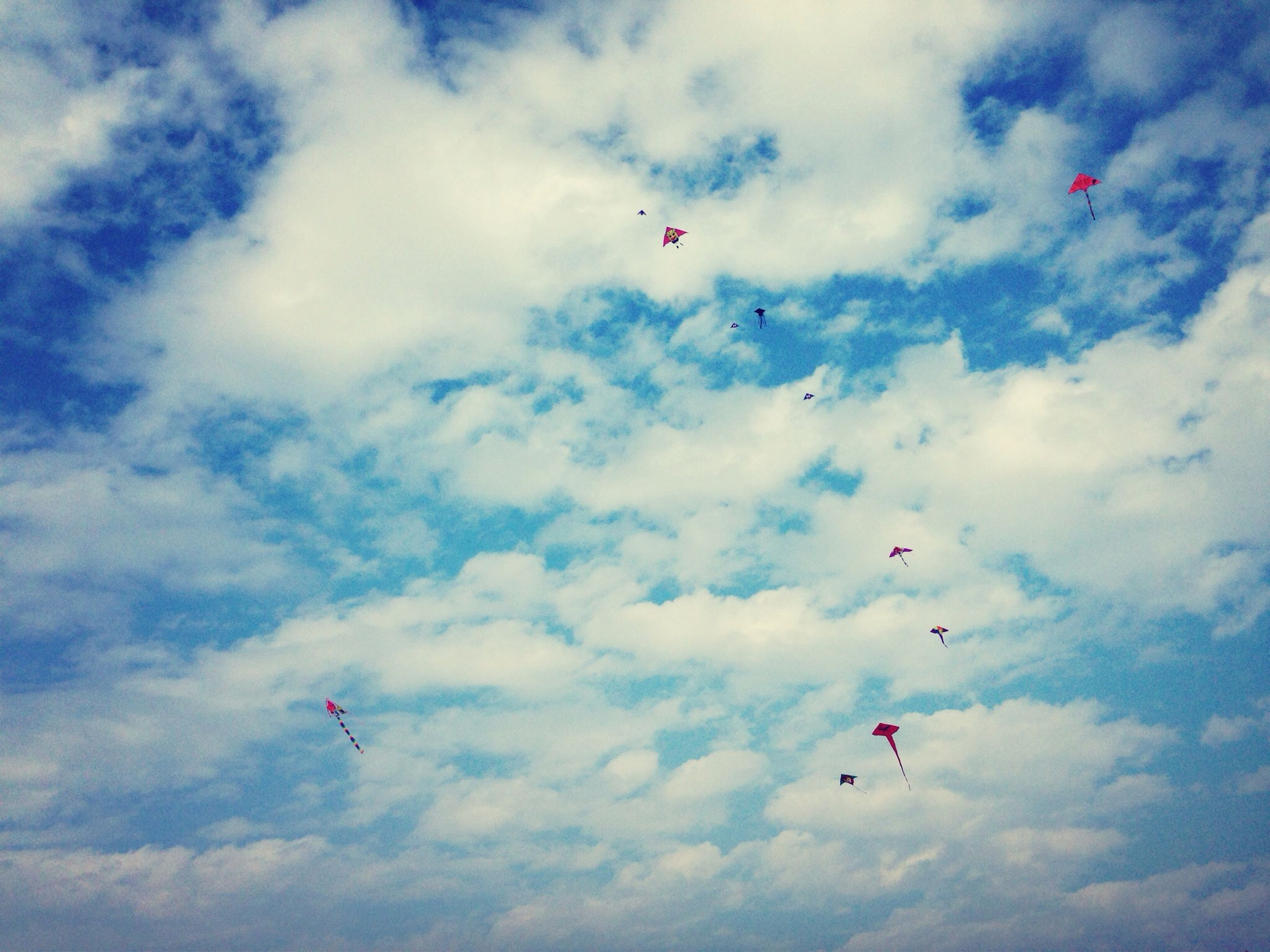 flying, mid-air, low angle view, sky, transportation, air vehicle, cloud - sky, airplane, mode of transport, parachute, blue, adventure, extreme sports, kite - toy, paragliding, freedom, travel, cloud, day, on the move