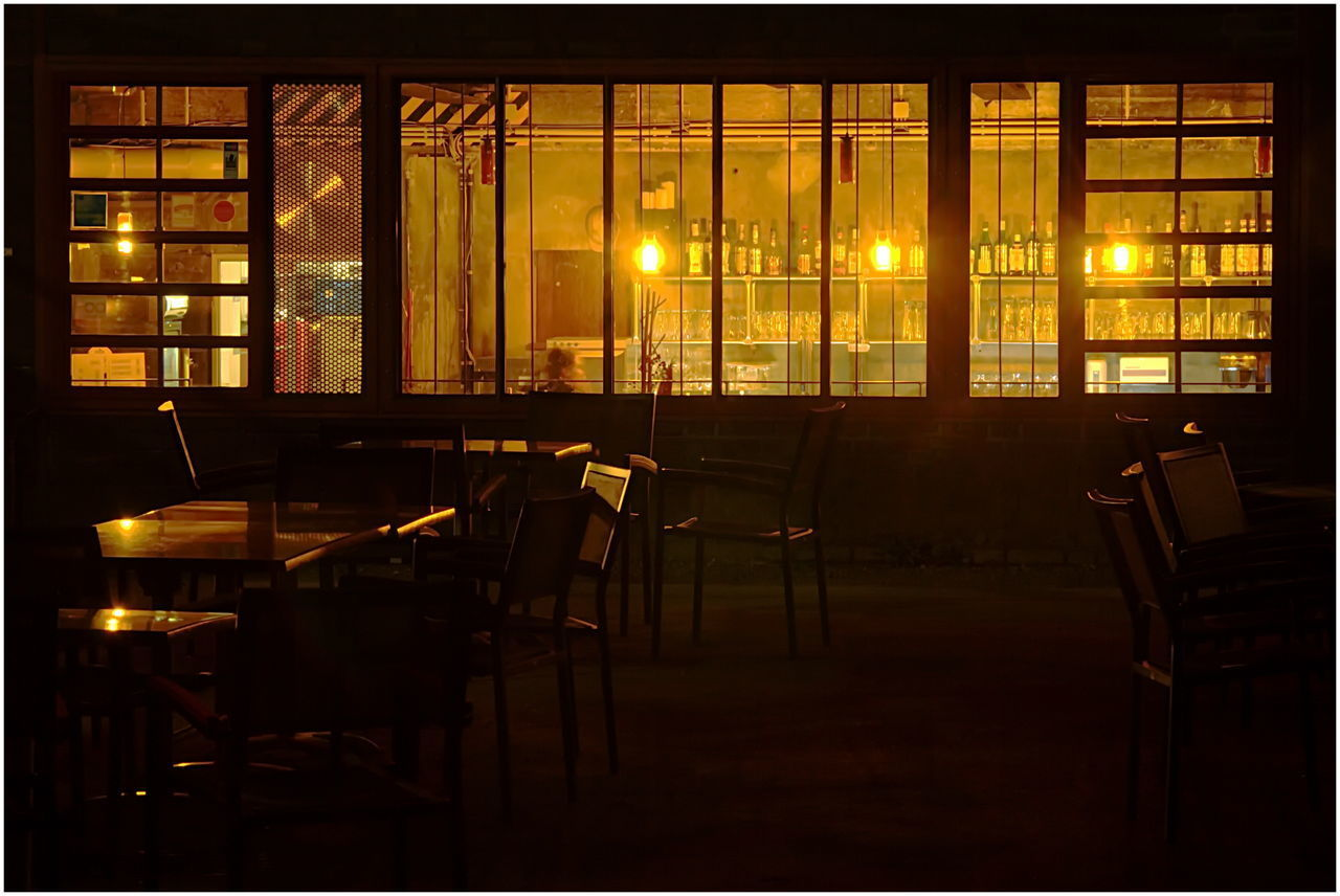 window, seat, table, chair, transparent, architecture, glass - material, illuminated, indoors, no people, restaurant, lighting equipment, absence, built structure, empty, education, night, business, transfer print, furniture, glass, electric lamp