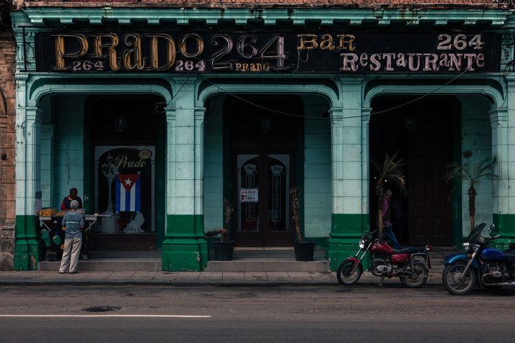 A street seller offers his food in front of a restaurant along Paseo Del Prado, Havana, Cuba. Arch Architecture Cuba Cuban Cuban Flag Cuban Life Daily Life Exterior Exterior Building Flag Green Building Havana Motorcycles People Porch Selling Streetvendor Trade