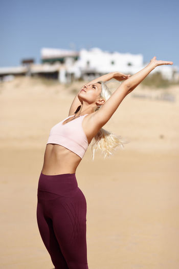 Woman exercising at beach in sunny day