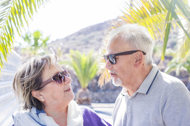 Close-Up Of Couple Wearing Sunglasses With Face To Face Against Mountain