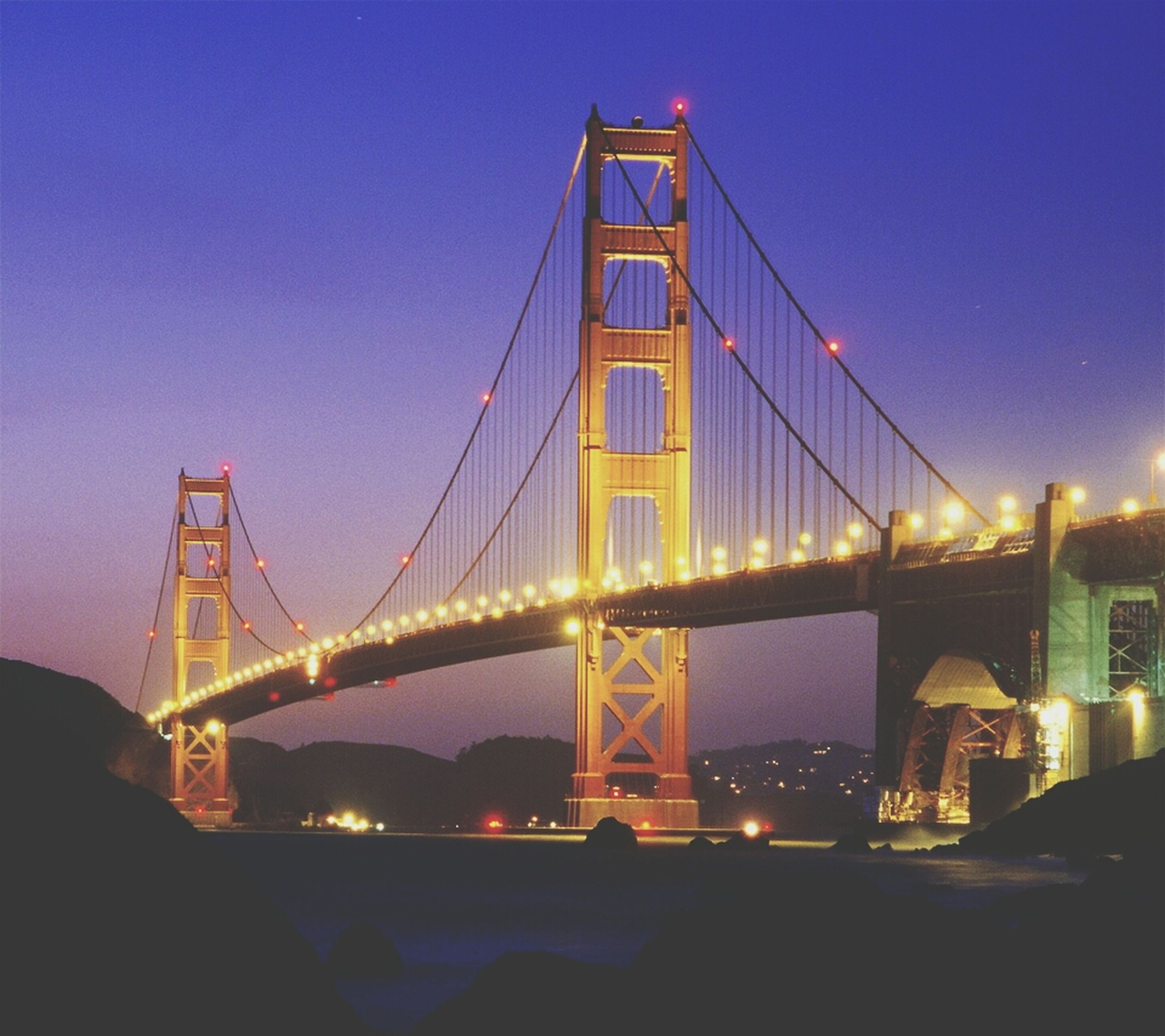 architecture, built structure, connection, suspension bridge, bridge - man made structure, engineering, international landmark, famous place, travel destinations, illuminated, capital cities, city, night, clear sky, tourism, golden gate bridge, travel, cable-stayed bridge, transportation, bridge
