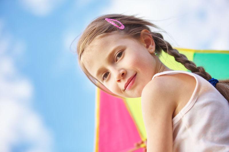 Portrait of cute girl against sky