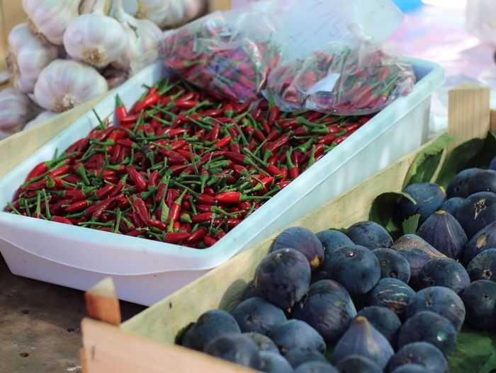 Chili Peppers And Figs In Containers At Market For Sale