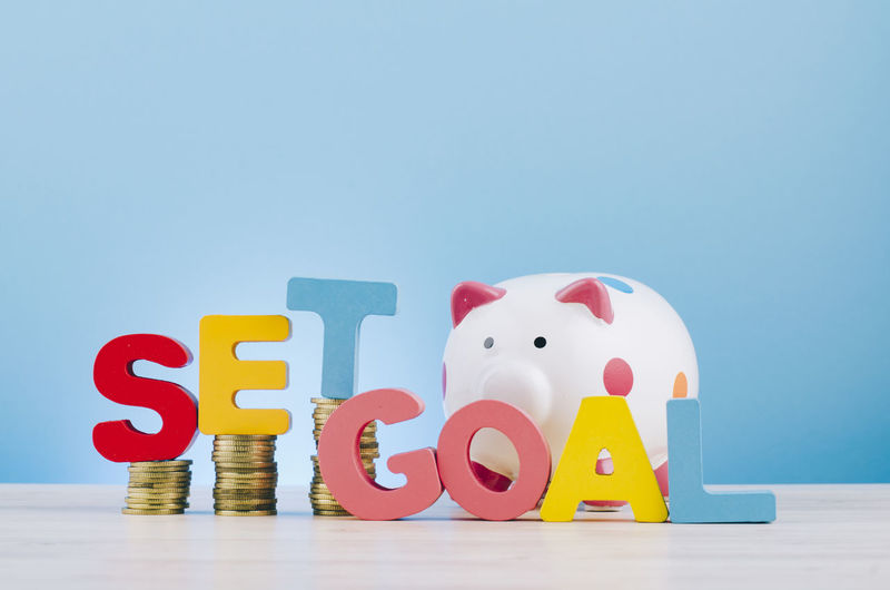 financial and saving money concept, word SET GOAL over piggy bank with stacking coins on wooden desk Indoors  Still Life Studio Shot Investment Finance Blue Business Currency Copy Space Savings Blue Background Colored Background No People Table Red Coin Toy Wealth Piggy Bank Cut Out Economy