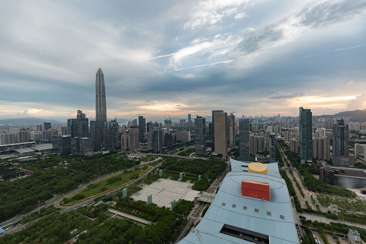 Aerial view of city buildings against cloudy sky