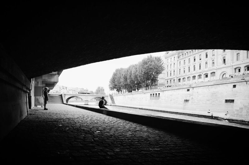 People on bridge over canal in city