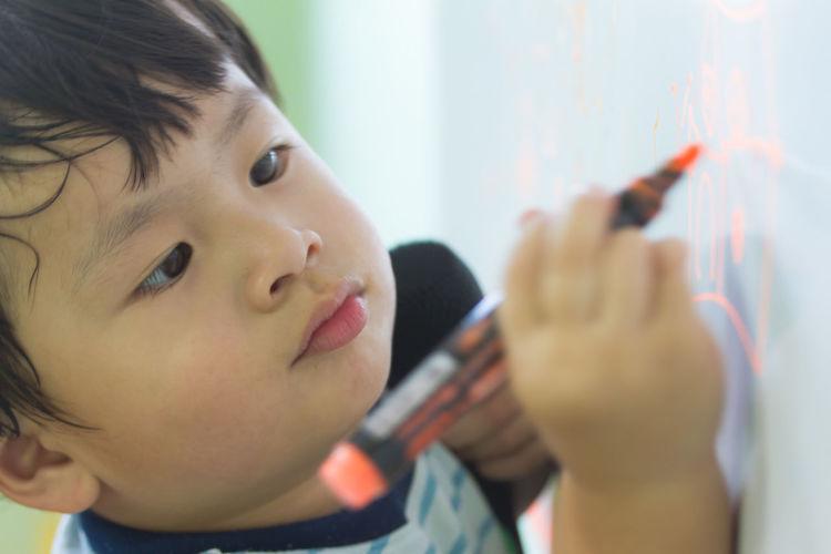 Close-Up Of Cute Boy Writing On Whiteboard