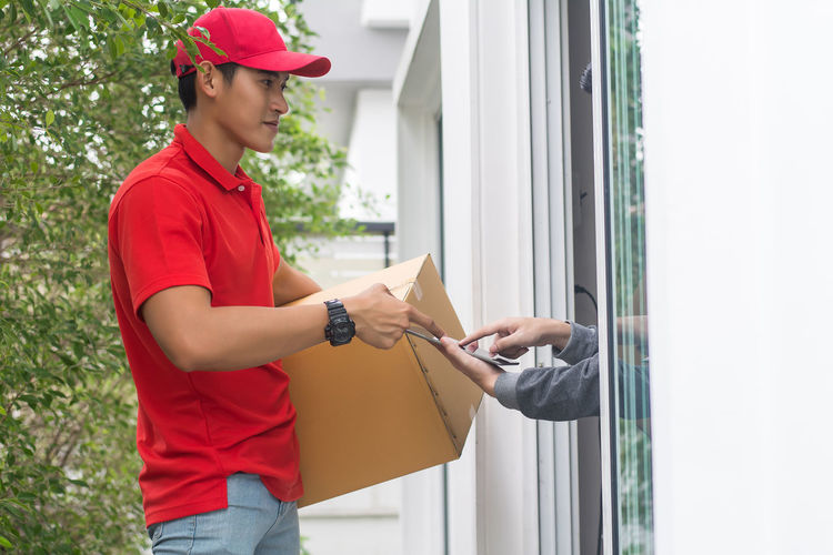 Young man delivering package to customer at doorway