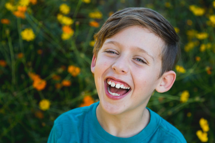 Close-up portrait of laughing boy against flowers