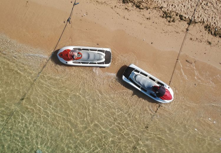 High angle view of speedboats moored at beach