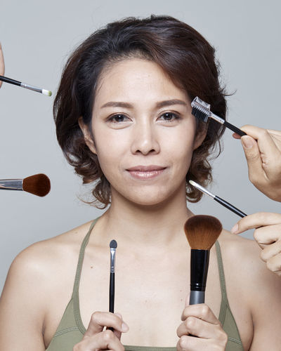 Portrait of mid adult woman holding make-up equipment against gray background